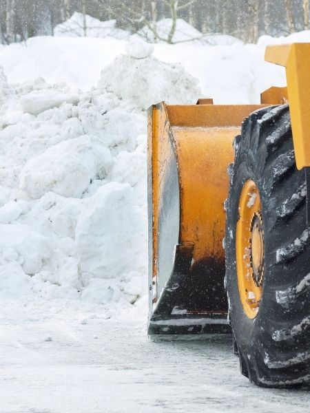 tractor dumping bucket of snow from parking lot